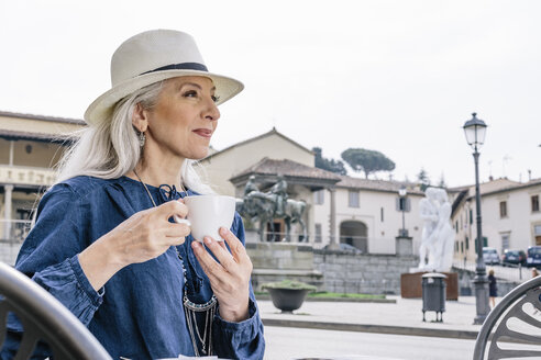Mature woman drinking coffee at sidewalk cafe, Fiesole, Tuscany, Italy - CUF12070
