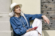 Stylish mature woman sitting outside church, Fiesole, Tuscany, Italy - CUF12073