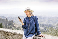 Stylish mature woman looking at smartphone, Fiesole, Tuscany, Italy - CUF12079