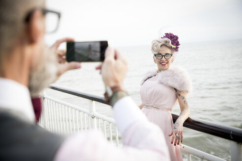 Over shoulder view of man taking photograph of 1950's vintage style mature woman on pier - CUF12094