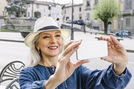 Mature woman taking smartphone selfie at sidewalk cafe, Fiesole, Tuscany, Italy - CUF12172
