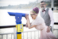 1950's vintage style couple looking through coin operated binoculars on pier - CUF12184