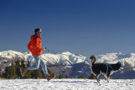 Man running with dog in snow covered mountain landscape - CUF12208