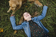 Young girl lying on grass looking up at her Golden Retriever - CUF12241