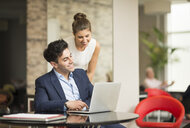 Businessman and woman looking at laptop in office - CUF12310