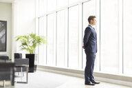 Confident businessman looking through office window - CUF12313