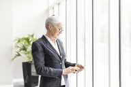 Mature businesswoman looking at smartphone by office window - CUF12316