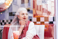 Mature woman in baseball jacket looking through window from 1950's diner - CUF12319