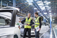 Apprentice car inspector with mentor in car factory - CUF12337