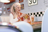 Mature woman in baseball jacket eating burger in 1950's diner - CUF12358