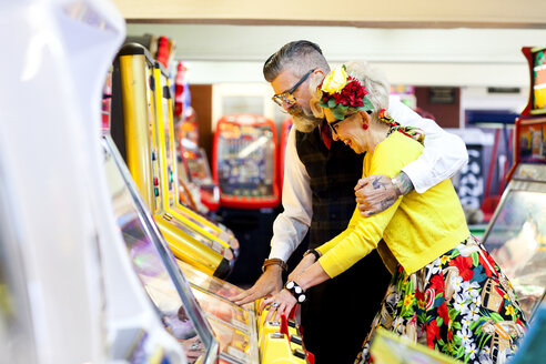 Couple enjoying themselves in amusement arcade, Bournemouth, England - CUF12361