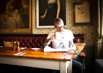 Quirky man reading newspapers in bar and restaurant, Bournemouth, England - CUF12376