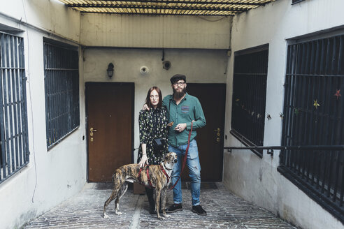 Portrait of cool couple with dog outside apartment - CUF12403