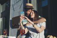 Couple taking smartphone selfie at sidewalk cafe - CUF12418