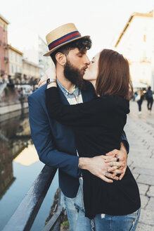 Hipster couple kissing by city canal - CUF12421