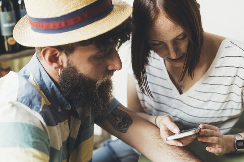 Couple looking at smartphone in bar - CUF12460