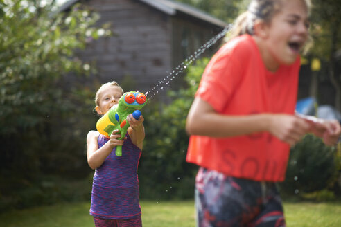 Boy squirting his teenage sisters with water gun in garden - CUF12466