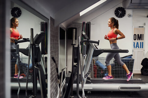 Young woman training, running on gym treadmill - CUF12502