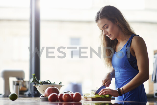 Young woman at kitchen table slicing vegetables - CUF12526 - Matt Lincoln/Westend61