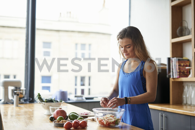 Young woman at kitchen table preparing salad bowl - CUF12529 - Matt Lincoln/Westend61