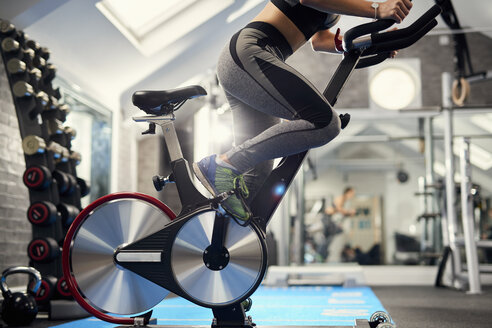 Neck down view of young woman training, pedalling exercise bike in gym - CUF12547