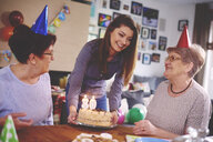 Daughter presenting birthday cake to mother at birthday party - CUF12580
