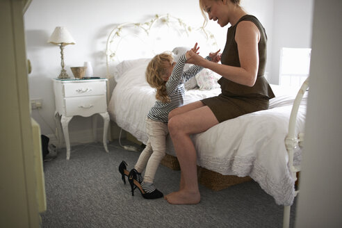 Mother holding daughter balancing in high heel shoes - CUF12595