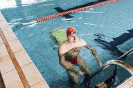 Senior man using ladder in swimming pool - CUF12604