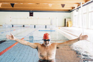 Senior man with open arms in swimming pool - CUF12616