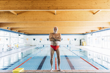 Senior man standing by swimming pool - CUF12619