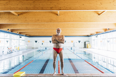Senior man standing by swimming pool - CUF12619