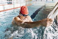 Senior man using ladder in swimming pool - CUF12790