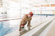 Senior man climbing up side of swimming pool - CUF12793