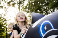 Two sisters playing on inflatable whale in park - CUF12965