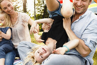 Father turning daughter upside down at family picnic in park - CUF12989