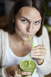 Woman drinking green smoothie with straw - CUF13112