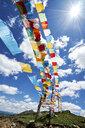 Rows of colourful prayer flags against blue sky, Zhagana, Gansu, China - CUF13166