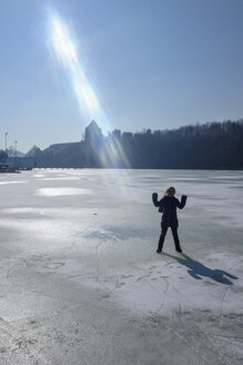 Girl standing on frozen lake, sun beam - HAMF00321