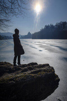 Woman standing on lakeshore in winter against the sun - HAMF00327