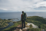 Norway,, Lofoten, Moskenesoy, Backpacker standing on cliff, looking to the Atlantic Ocean - GUSF00762