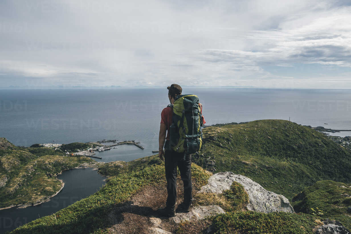 Norway,, Lofoten, Moskenesoy, Backpacker standing on cliff, looking to the Atlantic Ocean - GUSF00762 - Gustafsson/Westend61