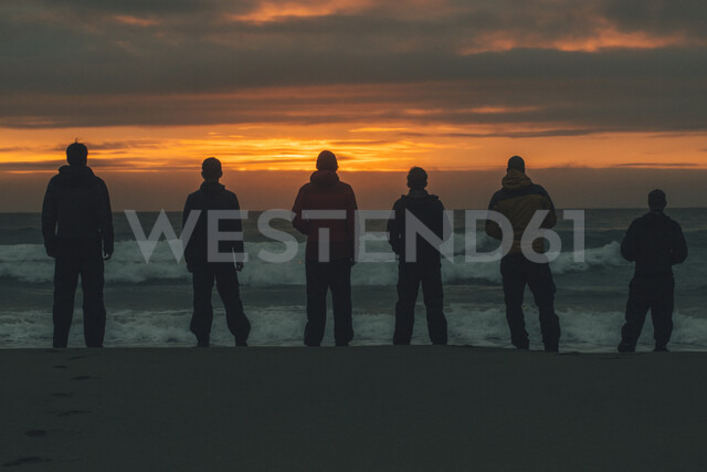 Norway, Lofoten, Moskenesoy, Young men standing at Bunes Beach at sunset - GUSF00777