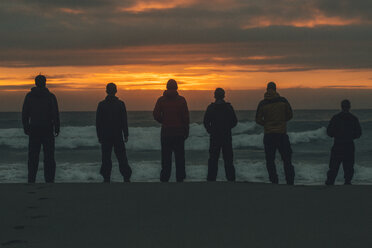 Norway, Lofoten, Moskenesoy, Young men standing at Bunes Beach at sunset - GUSF00777