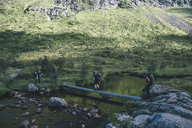 Norway, Lofoten, Moskenesoy, Young men crossing water at Agvatnet - GUSF00783
