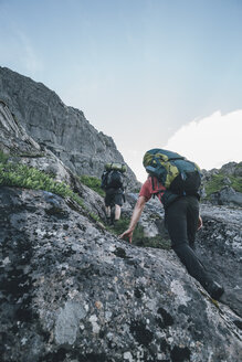 Norway, Lofoten, Moskenesoy, Young man hiking in the mountains - GUSF00810