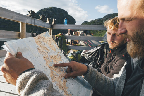 Norway, Lofoten, Moskenesoy, Young men discussing directions, holding map - GUSF00813