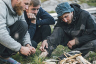 Norway, Lofoten, Moskenesoy, Young men starting a camp fire - GUSF00816