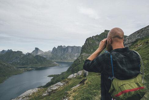 Norway, Lofoten, Moskenesoy, Man looking over Kjerkefjord - GUSF00819