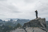 Norway, Lofoten, Moskenesoy, Young man standing at Hermannsdalstinden, looking over Kjerkefjord - GUSF00831