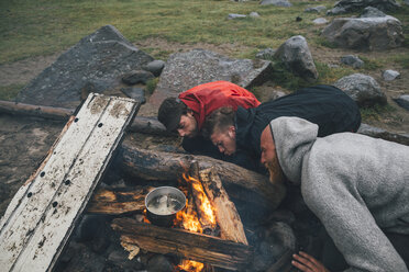 Norway, Lofoten, Moskenesoy, Three men fanning the flames of a camp fire at Bunes Beach - GUSF00846